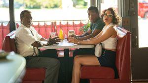 Tre afroamerikaner sitter i en diner på femtiotalet och ser nervöst mot kameran.