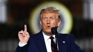 Donald Trump talar i mikrofon och håller upp pekfingret.