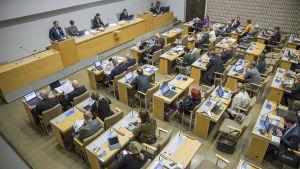 Människor sitter samlade till fullmäkitgemöte, alla vid varsitt arbetsbord. Längst fram i salen finns mötets ordförande. Bilden är tagen snett uppifrån