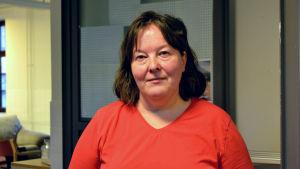 En kvinna med brunt axellångt hår och röd v-ringad blus tittar rakt in i kameran.