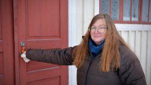 Lilian Petterson-Smeds står framför Svedbergska skolan i Munsala. Dörren är röd och hon är på väg att öppna den.