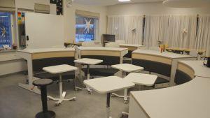 Modern lärmiljö med vita skolbänkar.