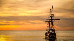 Ett segelfartyg från 1800-talet seglar mot solnedgången