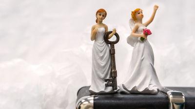 Naispari (kakkukoristeet) seisoo matkalaukun päällä. Toisella on iso avain kädessä.