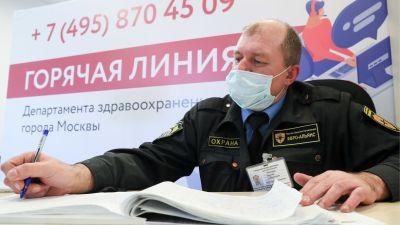 En säkerhetsvakt i uniform och munskydd antecknar i en bok. Han sitter framför ett plakat med text på ryska.