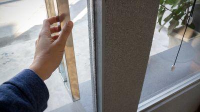 En hand ska ta i ett dörrhandtag.