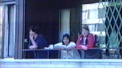 Bild på publik som följer med gisslandramat i Borgå 2002 från balkongen i grannhuset