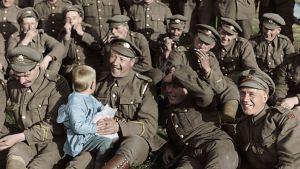 Soldater sitter uppställda och spelar munspel och skrattar, en av soldaterna håller ett litet barn i famnen.