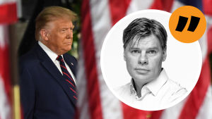 Donalnd Trump mellan en massa amerikanska flaggor.