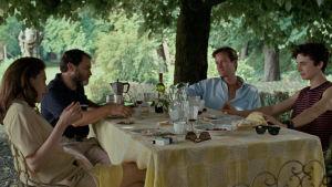 Familjen Perlman och Oliver (Armie Hammer) sitter vid ett bord utomhus, under ett träd och äter.