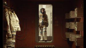 Monte (Robert Pattinson) i rymddräkt, står i en dörröppning.