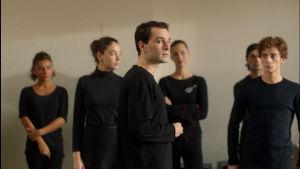 Irakli (Bachi Valishvili) står omgiven av de andra dansarna, Merab (Levan Gelbakhiani) syns vid hans sida.
