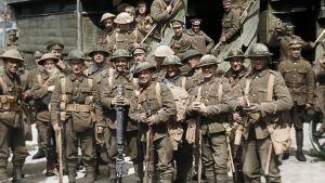 Soldater under första världskriget som står uppställda vid en tågvagn och ser glada ut.