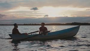 Tareq (Boodi Kabbani) och Leevi (Janne Puustinen) i en roddbåt i solnedgången.