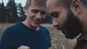 Leevi (Janne Puustinen) och Tareq (Boodi Kabbani) står bredvid varandra på en sommaräng.