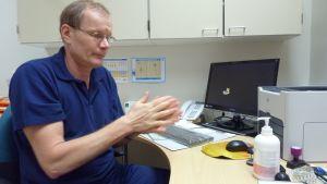 Ledande överläkare Ilkka Pyrrö smörjer sina händer med handsprit.