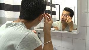 Stefan Eklöf sminkar sig framför spegeln.