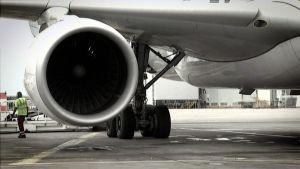 Lentokoneen siipi ja moottori lentokentällä.