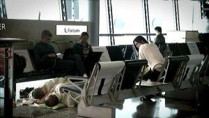 Matkustajia odottamassa lentokentällä, lattialla kaksi ihmistä nukkuu.