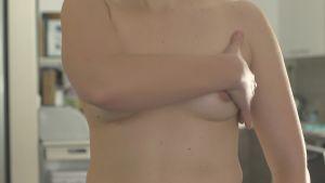 En kvinna med bara bröst känner efter knölar.