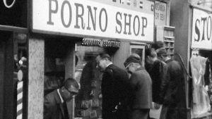 Miehiä katsomassa pornokaupan ikkunaa