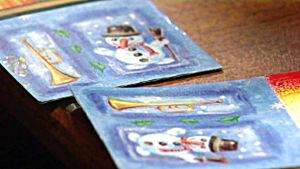 Närbild av två dominobrickor med en tecknad bild av en glad snögubbe med hatt och kvast och en stående trumpet på sidan.