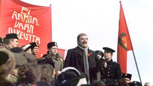 Risto Mäkelä johtaa puhetta torilla elokuvassa Luottamus.