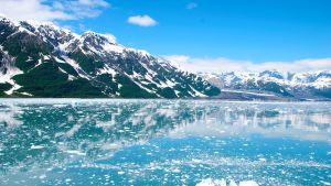 Maisema Alaskan aurinokoiselta jäämereltä, lumihuippuiset vuoret heijastuu mereen.