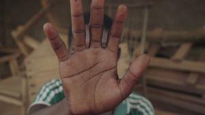 Barn som håller handen mot kameran.