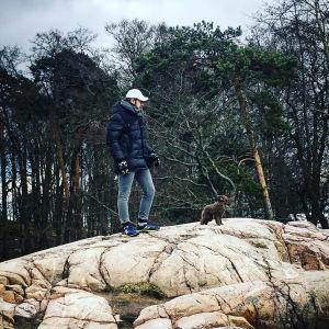 Oopperalaulaja Waltteri Torikka kalliomaisemassa koiransa kanssa.