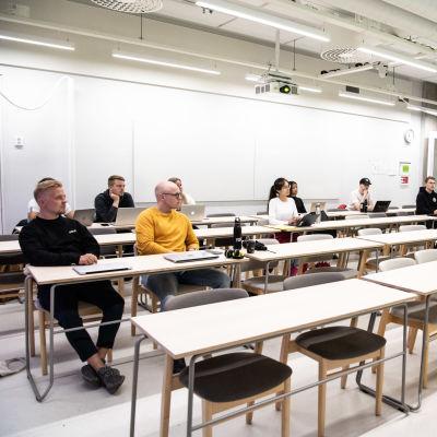 Ett tiotal studerande sitter glest i en föreläsningssal. Till vänster sitter en man i gul tröja, till höger står läraren.