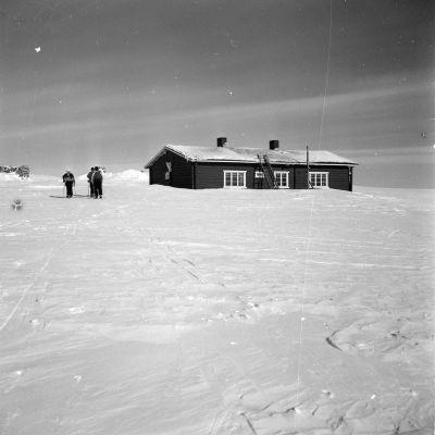 Retkeilijät hiihtämässä Ounastunturin matkailumajalle