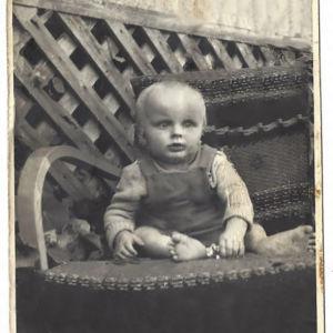 Vanhassa kuvassa pieni poika istuu hajasäärin tuolilla ulkona talon edessä.