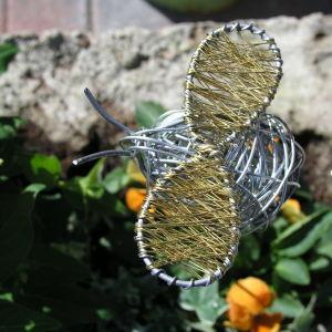 En humla i luffarslöjd som pryder en blomrabatt.