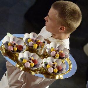 En servitör med Nobelmiddagens efterrätt