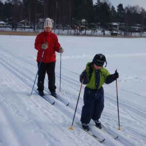 Aikuinen ja lapsi hiihtävät peräkkäin lumen peittämällä jäällä