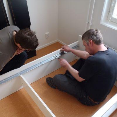 två män skruvar ihop en hylla