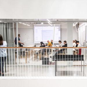 Elever i klassrum med glasvägg på Aalto universitet.
