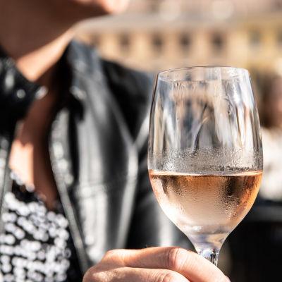 Ett vinglas i handen på en kvinna.