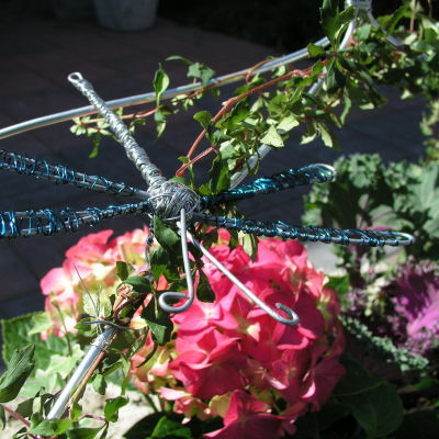 En trollslända i luffarslöjd som dekorerar ett klängväxtstöd för en murgröna.