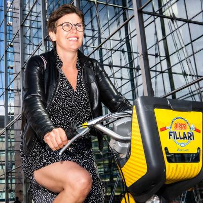 Nainen ajaa kaupunkipyörällä.