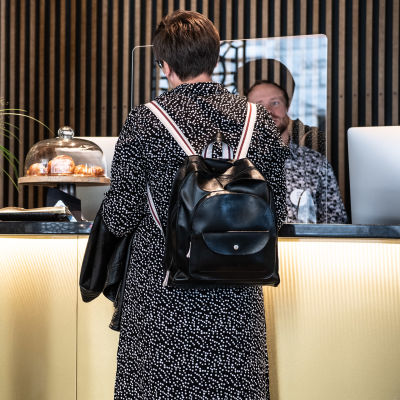 Kvinna bakifrån vid en hotellreception.