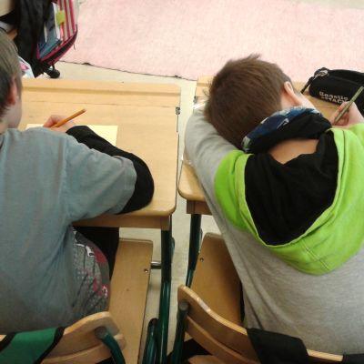 Kaksi alakoululaista poikaa on kumpartunut pulpettinsa ylle kirjoitustehtävään.