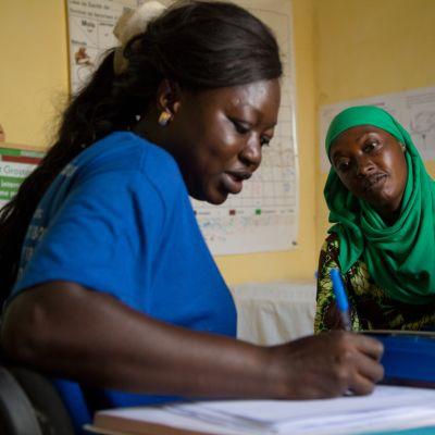 nainen klinikan vastaanotolla kuuntelee, terveydenhoitaja kirjoittaa paperiin