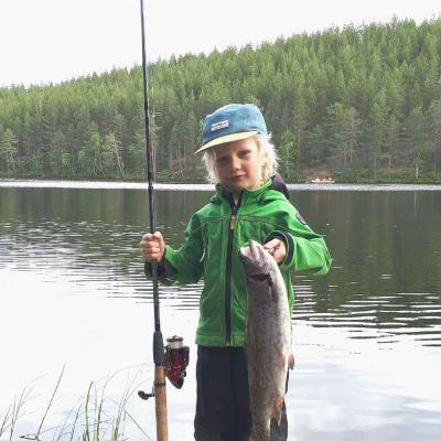 Oiva Blomberg järvimaisemassa virveli ja iso lohi käsissään Kuhmon Syväjärvellä.