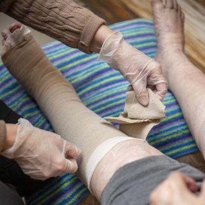 Lähihoitaja kietoo vanhuksen jalkaan tukisidettä.