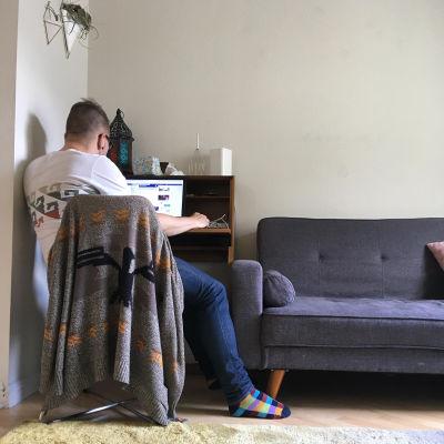 Mies kotona tietokoneen ääressä.