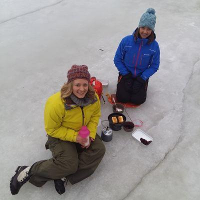 Två kvinnor som sitter på isen och lagar mat på ett friluftskök.