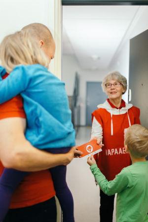 en barnfamilj får ett presentkort av en frivilligarbetare