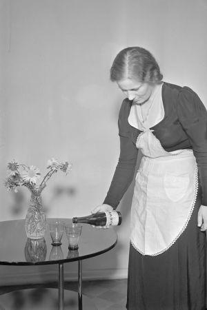 Dam i förkläde häller upp källvattnet Kirvu i ett glas från en flaska.